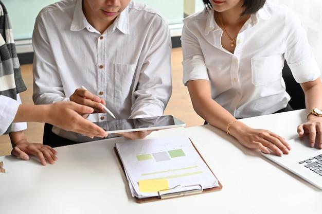 若いビジネス相談と作業テーブルと手にデジタルタブレットの会議。