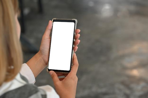 空白の画面表示でスマートフォンを使用して若い女性。