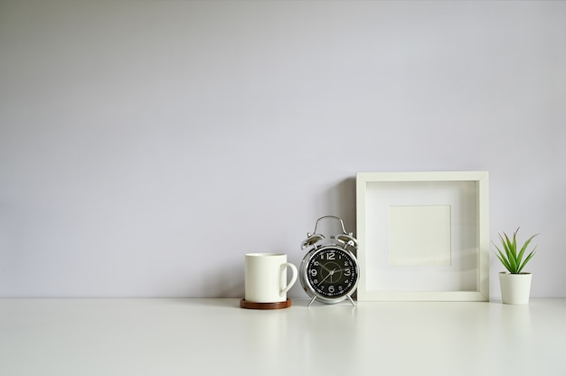目覚まし時計。コピースペースを持つ白いテーブルにコーヒー、フォトフレーム、植物の装飾。