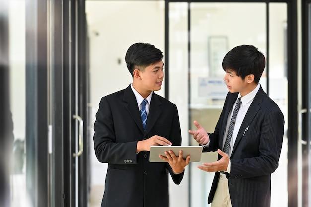 Два молодых бизнесмена консультируются и встречаются с деловыми беседами.