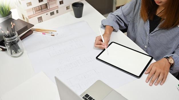 建築プロジェクトの女性作業デジタルタブレット図面アーキテクチャプロジェクト。