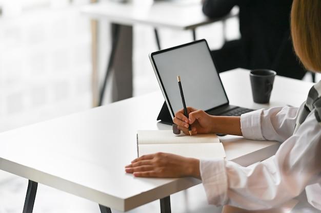 Взгляд конца-вверх молодой коммерсантки работая на его плане писать идею на тетради с цифровой таблеткой.