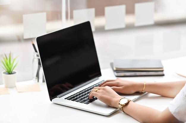 Мотивированная бизнес-леди фокусируя на проекте пока использующ портативный компьютер, подрезанное фото съемки.