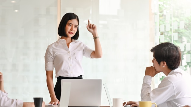 会議室で彼女のアイデアを説明する若い情熱的な実業家