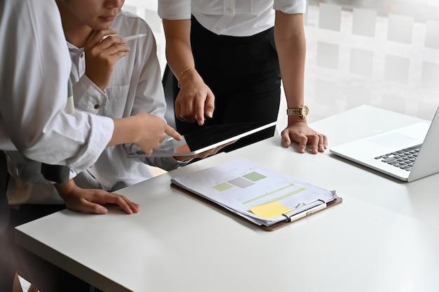 テーブルの上のデジタルタブレットと若いチームのスタートアップ事業の会議。