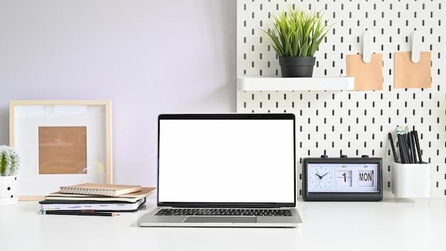 空のモニターコンピューターとワークスペーステーブルにラップトップ、ペグボード、オフィス用品。