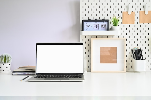 白いテーブルオフィスのワークスペースノートパソコン、ペグボード、オフィス用品。