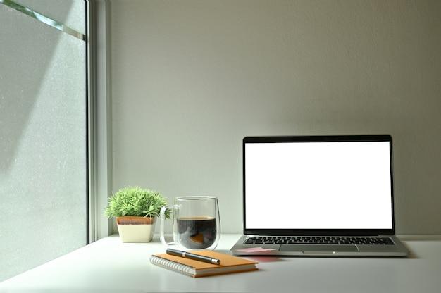 モックアップラップトップコンピューター、コーヒー、ノート、窓の近くのコーヒーとペン。