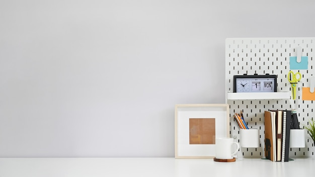 Рабочая область канцелярских товаров, кофе и фото рамка на белом творческий стол с копией пространства.