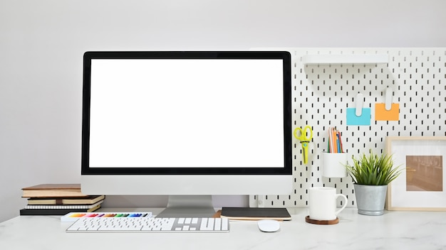 空のスクリーンコンピューターと大理石のテーブルに事務用品を備えた現代的なワークスペース。