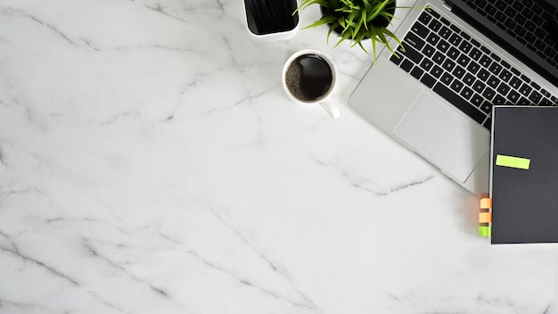 トップビューオフィスデスクラップトップ、コーヒーカップ、事務用品と大理石の白いテーブル。