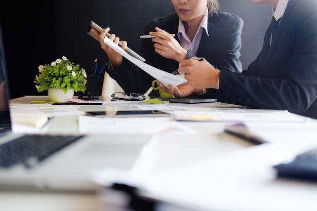Бизнес-концепция, команда аудита, работающая с планшетным компьютером и бумажным отчетом в финансовом офисе.