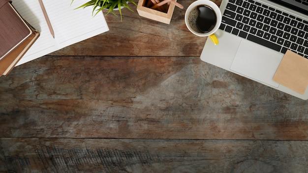 木製の机の上のノートパソコン、ノート、鉛筆、コーヒーカップのトップビュー