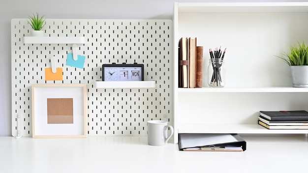 棚とワークスペーステーブル上のオフィス用品付きペグボード