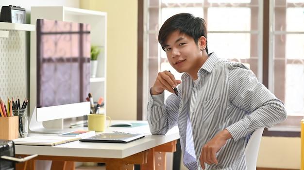 Азиатский человек сидя на рабочем месте домашнего офиса творческом.