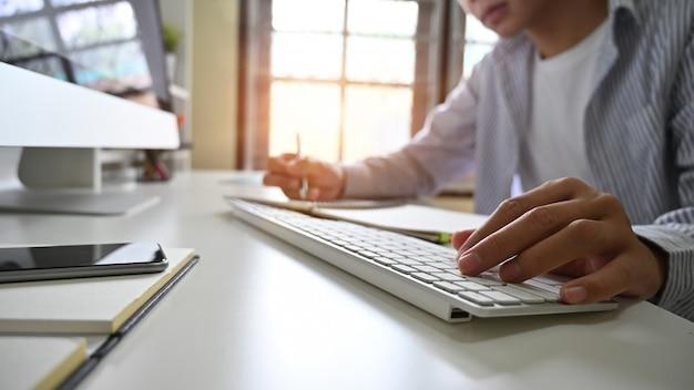 男の手がホームオフィス職場にコンピューターのキーボードを入力します。