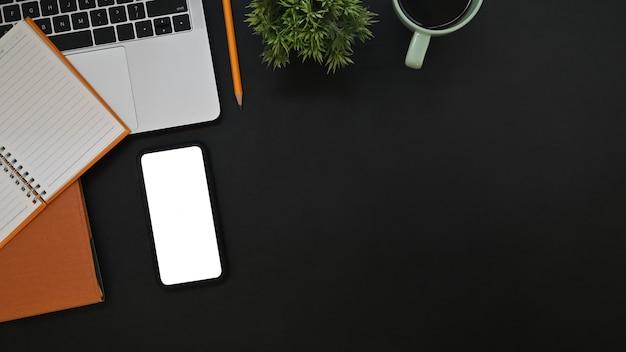 オフィスの机の上のスマートフォン、ラップトップ、ノートブック、鉛筆、コーヒーカップの空の画面でトップビュー黒革。