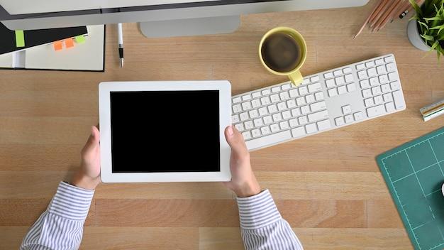 Таблетка места для работы взгляд сверху держа руки человека с выше стола офиса таблицы.