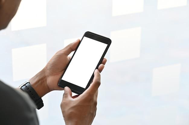 空白のコピースペース画面を持つスマートフォンを保持しているクローズアップ男の手