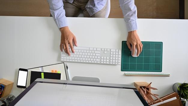 Вид сверху рабочей области с молодым человеком, с помощью компьютера