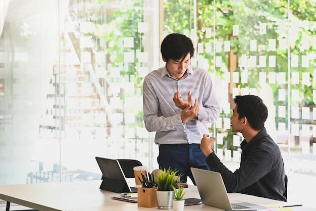近代的なオフィスで話している若い男性