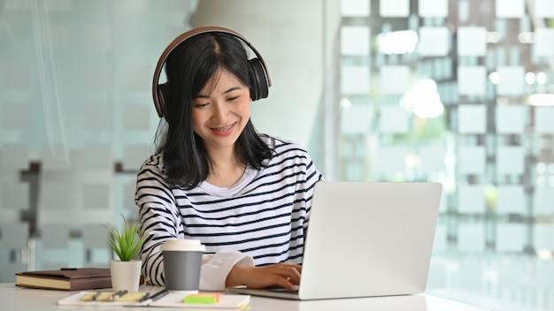 ラップトップを使用して、ヘッドフォンで歌を聴く若い女性