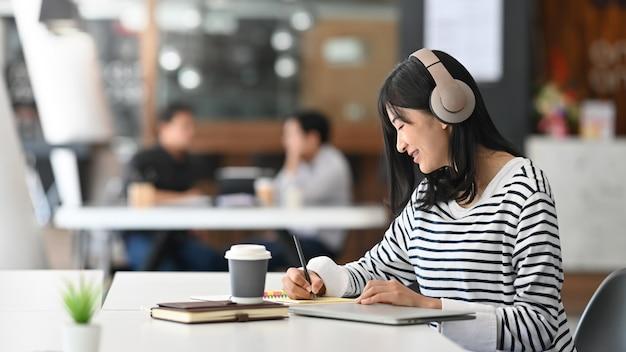 近代的なオフィスで音楽を書くと聴く若い創造的な女性