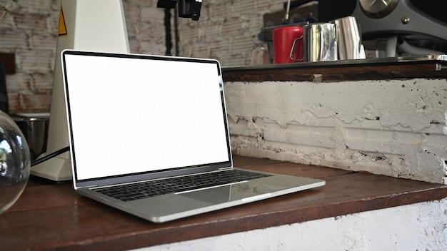 孤立した白い画面のコーヒーショップカウンターバーのラップトップコンピューターの空白の画面。