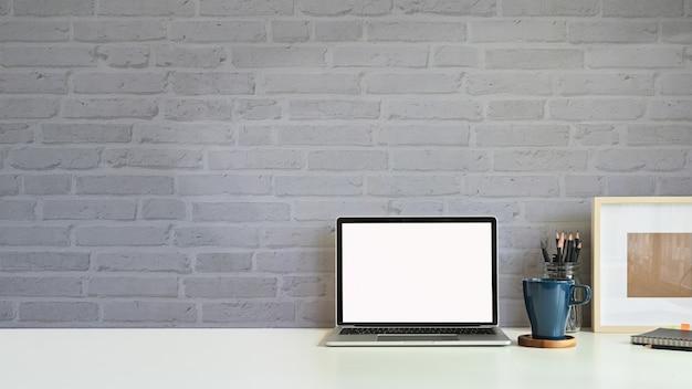 Скопируйте космический макет ноутбук, кружка кофе, карандаш с фоторамкой на рабочем месте стол кирпичной стены.