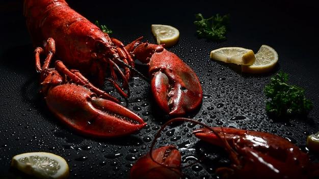 レモンとパセリのスタジオが付いた赤いロブスターは、ハイコントラストの暗い雰囲気を撮影しました。