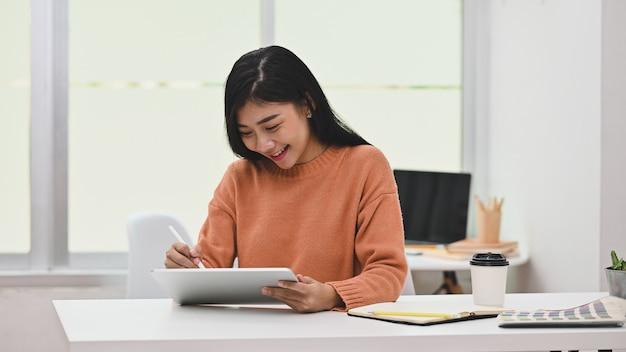 タブレットとペンを扱うアジアの創造的な女性。