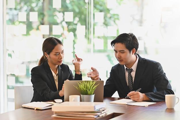 ディスカッションビジネス、ビジネス部門の同僚会議はオフィスの机で相談します。
