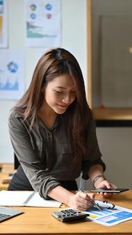 Молодой анализ женщины бухгалтерии на обработке документов с держать мобильный телефон.