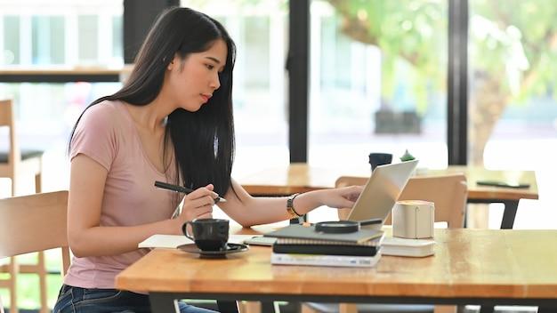 Молодая женщина работает на ноутбуке и держа перо на столе.