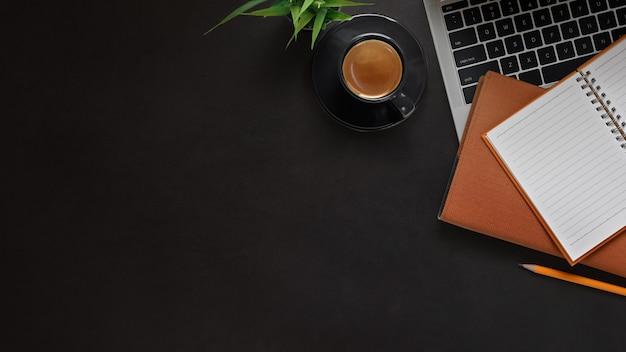 黒い革のテーブルの上にスペースオフィスデスクラップトップ、ノート、鉛筆、コーヒーをコピーします。