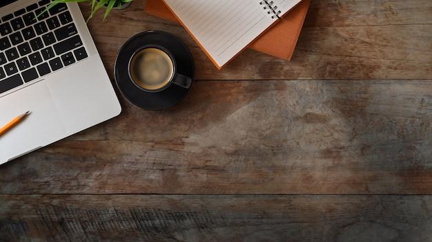 Плоский лежал офисный стол с ноутбуком, ноутбук, карандаш, растения и эспрессо на старый деревенский деревянный стол.