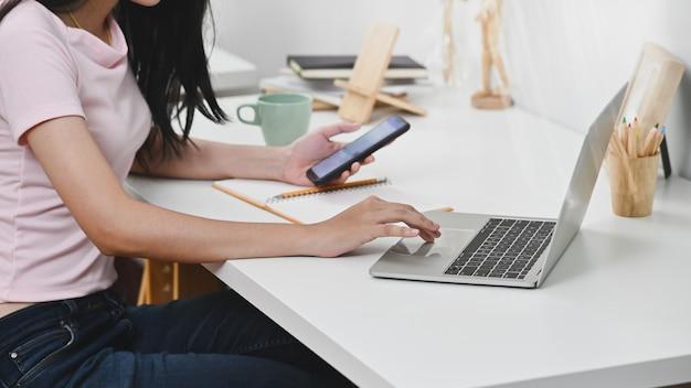 Молодая женщина, используя ноутбук и смартфон на рабочем месте.