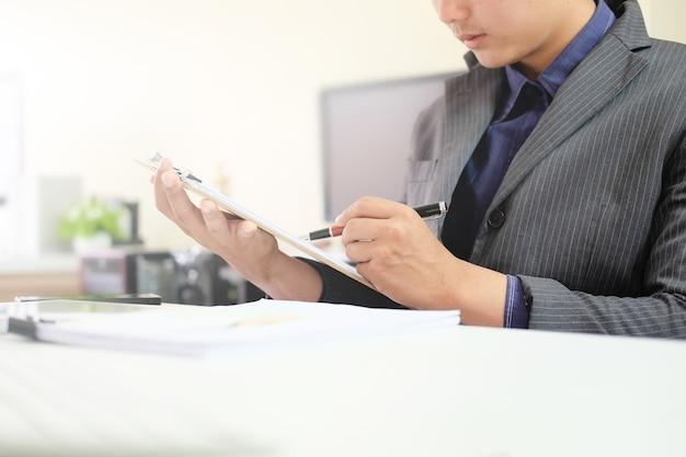 監査財務コンセプトのチャートボード上のビジネスマンのチェックリスト。