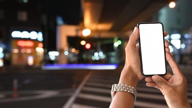 日本の都市景観に男の手にクローズアップモックアップスマートフォン。