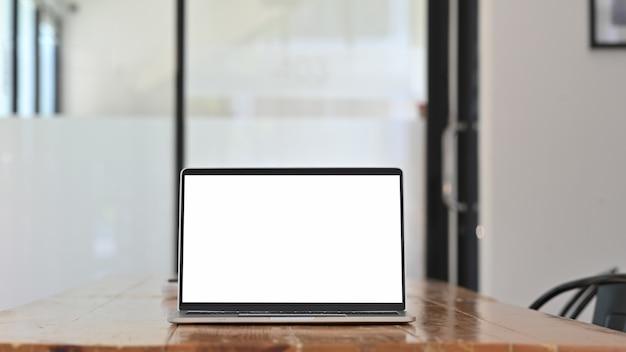 空白の画面を持つ木製テーブルの上のモックアップのラップトップコンピューター。