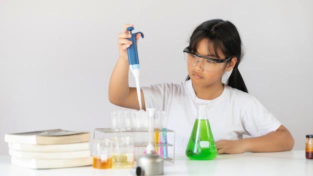 Молодая прелестная девушка держа стеклоизделия химии пока делающ научный эксперимент