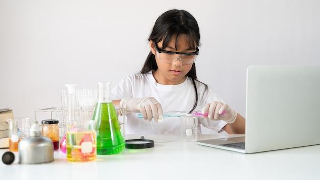 Фотография очаровательной школьницы, делающей научный эксперимент