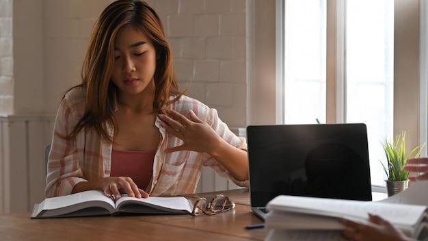 Талия вверх красивая женщина в полосатой рубашке, читая учебник сидя