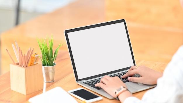Молодая творческая женщина, серфинг в интернете с помощью белого пустой экран ноутбука, сидя на современный деревянный стол.