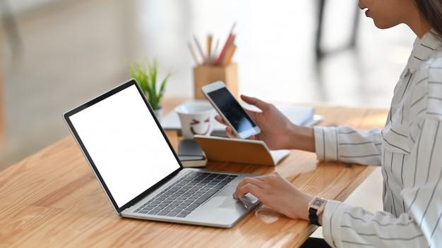 Молодая творческая женщина, серфинг в интернете с помощью белого ноутбука пустой экран и держа смартфон в руке, сидя на современный деревянный стол.