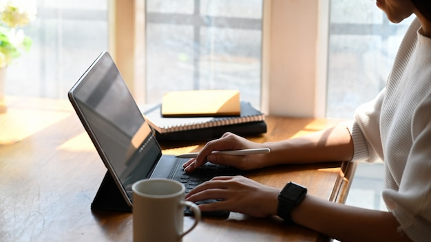 ホームオフィスのデジタルタブレットコンピューターに入力するショットの女性をトリミングしました。