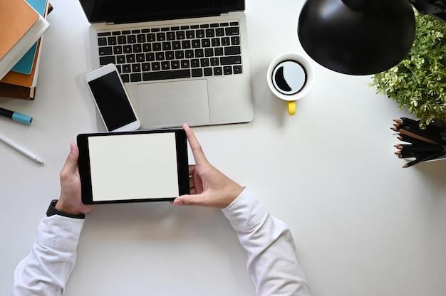 Над выстрелом бизнесмен, держащий планшетный компьютер с белым пустым экраном в руках на современном белом столе. вид сверху оргтехники, надевая современный рабочий стол. плоские прокладки.