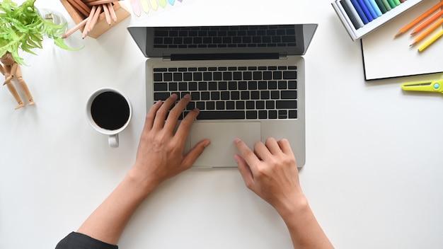 現代のラップトップに取り組んでいるトップビュー男の手。白いテーブルの上のオフィスのデスクトップ。