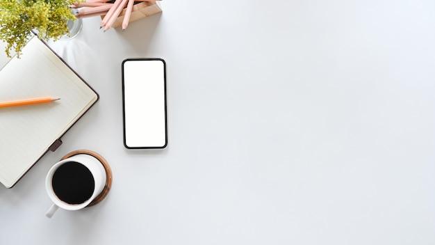 コピースペース平面図テーブルのオフィスの机の上のモックアップ携帯電話。
