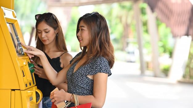 Молодая красивая женщина в платье держа хозяйственные сумки и вводя пароль на желтом автомате кассира рядом с ее другом который хорошо выглядеть в черном синглете на торговом центре.
